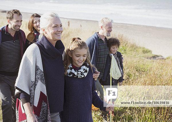 Smiling multi-generation family walking in beach grass
