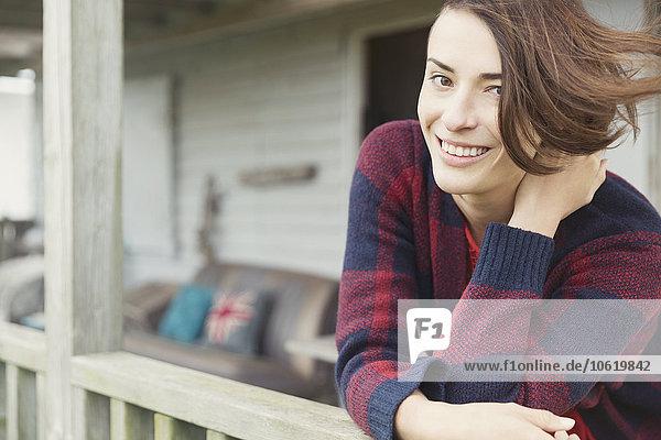 Portrait lächelnde brünette Frau auf der Veranda