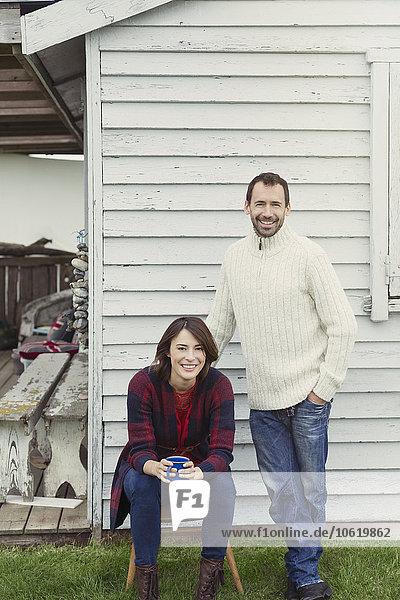 Portrait lächelndes Pärchen in Pullovern beim Kaffeetrinken vor dem Haus