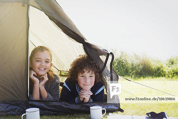 Portrait lächelndes Geschwisterpaar im Zelt