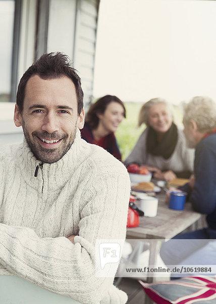 Portrait lächelnder brünetter Mann im Pullover auf Veranda mit Familie im Hintergrund