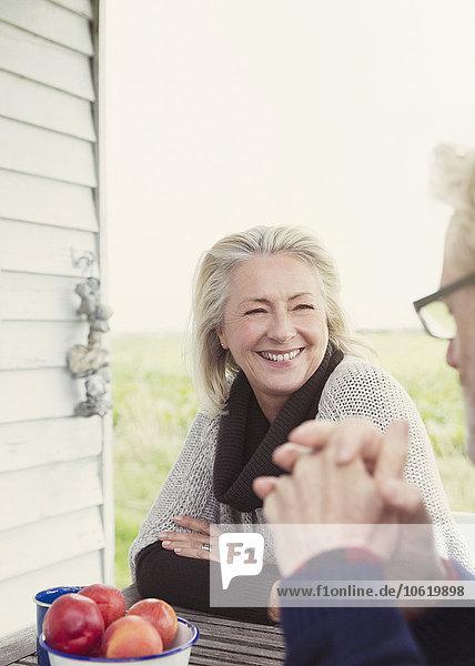Lächelndes Seniorenpaar im Gespräch am Verandatisch