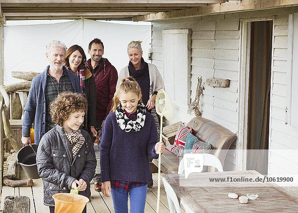 Mehrgenerationen-Familie mit Netzen und Eimer auf der Veranda
