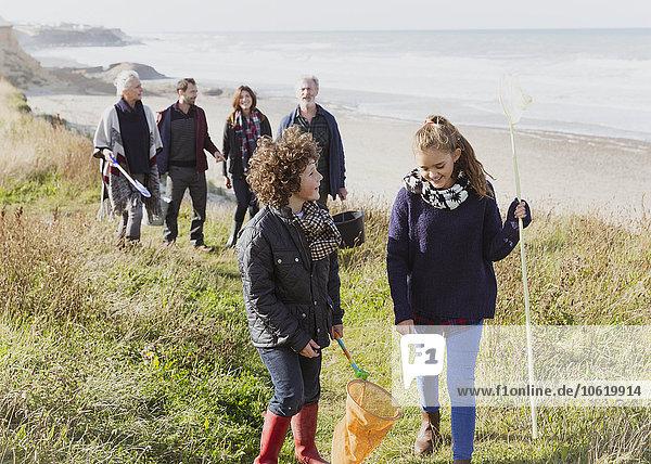 Mehrgenerationen-Familie mit Netzen auf sonnigem Grasstrandweg