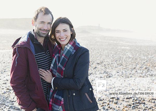 Porträt eines lächelnden Paares am sonnigen Felsenstrand