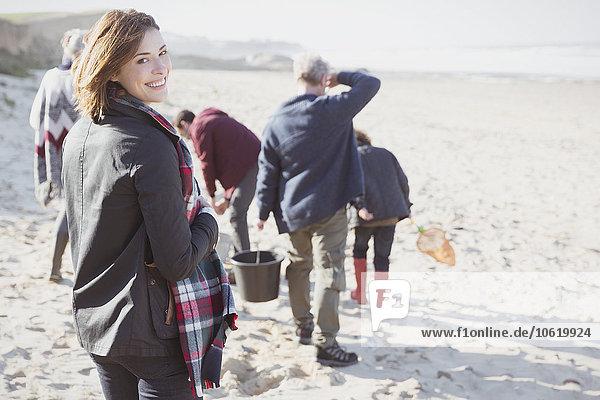 Porträt einer lächelnden Frau am sonnigen Strand mit Familie
