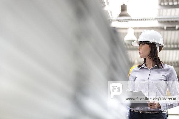 Geschäftsfrau mit Schutzhelm und Klemmbrett bei der Arbeit in der Fabrik