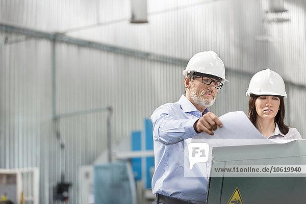 Ingenieure bei der Überprüfung von Bauplänen in der Fabrik