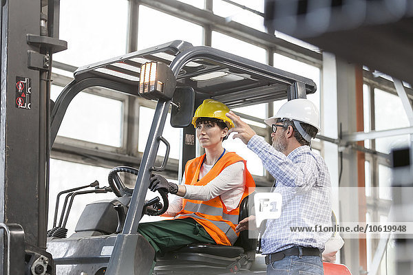 Supervisor directing worker driving forklift in factory