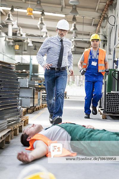 Arbeiter,  die auf einen gefallenen Mitarbeiter zugehen,  der bewusstlos in der Fabrikhalle liegt