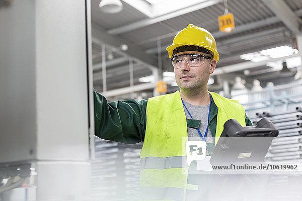 Arbeiter in Arbeitsschutzkleidung am Schaltschrank im Werk