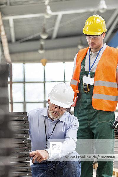 Ingenieur  der dem Arbeiter in der Fabrik Stahlteile erklärt.