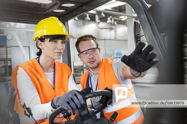 Arbeiterführung Mitarbeiter fahrender Gabelstapler im Werk