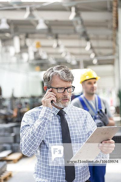 Ingenieur mit Zwischenablage beim Telefonieren in der Fabrik