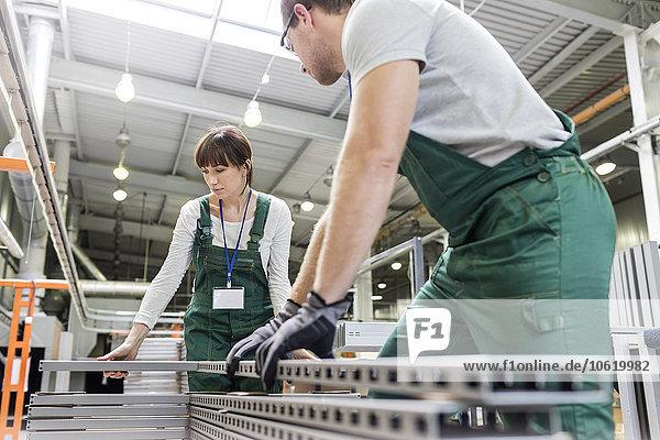Arbeiter bewegen Stahlteile im Werk