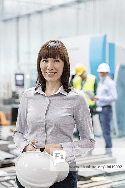Portrait lächelnder Ingenieur mit Schutzhelm in der Fabrik