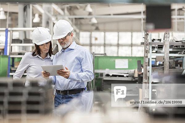 Ingenieure mit digitalem Tablett in der Stahlfabrik