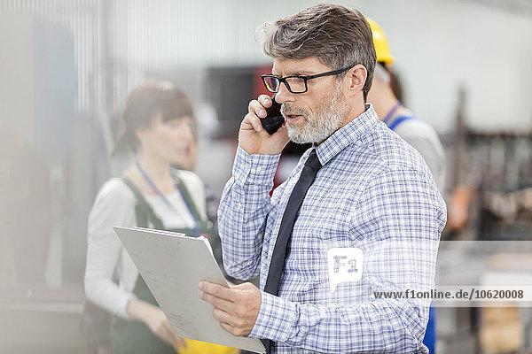 Geschäftsmann mit Zwischenablage beim Telefonieren in der Fabrik