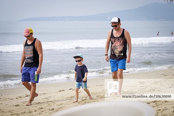 Mexico  Nayarit  two young men and little boy walking on a beach
