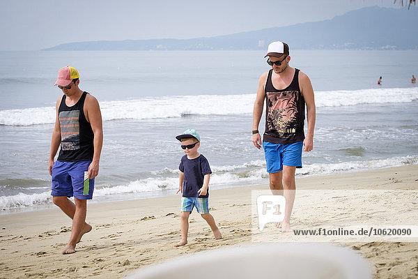 Mexiko  Nayarit  zwei junge Männer und ein kleiner Junge  die am Strand spazieren gehen.