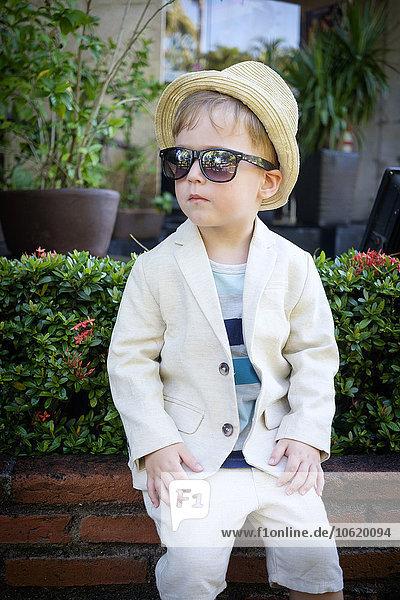 Porträt eines kleinen Jungen in modischem Anzug  Hut und Sonnenbrille  der auf einer Gartenmauer sitzt.