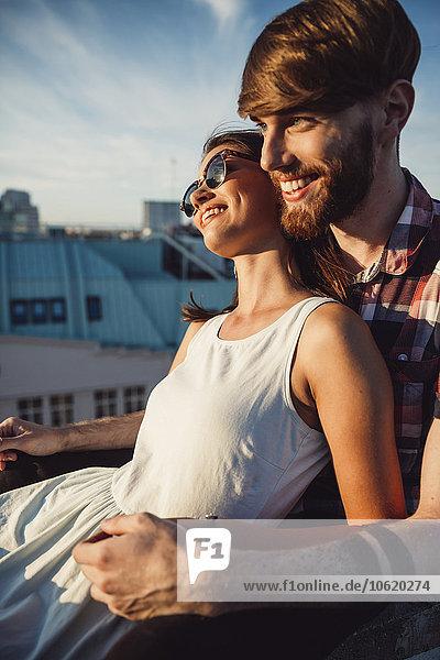 Österreich  Wien  Junges Paar genießt romantischen Sonnenuntergang auf der Dachterrasse