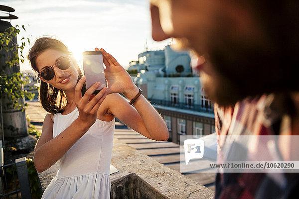 Österreich  Wien  lächelnde junge Frau beim Fotografieren ihres Freundes auf einer Dachterrasse