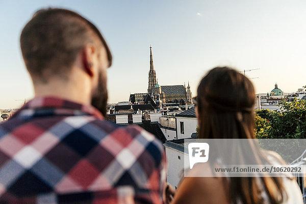 Österreich  Wien  Rückansicht des jungen Paares auf der Dachterrasse mit Blick auf den Stephansdom