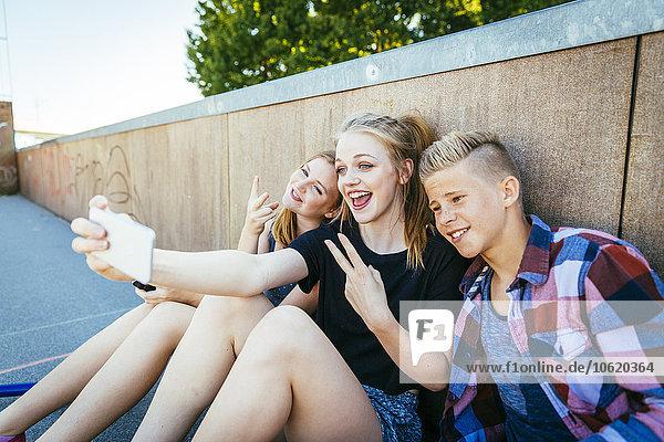 Drei fröhliche Teenager im Freien mit einem Selfie