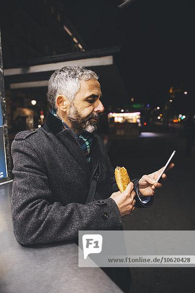 Österreich  Wien  Mann mit Käse Carniolan Wurst und Smartphone bei Nacht
