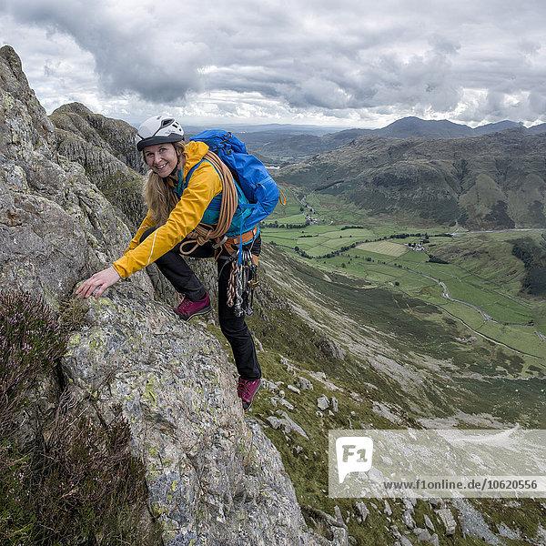 UK  Lake District  Great Langdale  Frau krabbelt auf Pike of Stickle