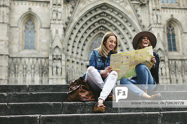 Spanien  Barcelona  zwei glückliche junge Frauen beim Kartenlesen auf der Treppe