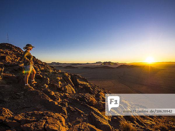 Afrika  Namibia  Hardap  Hammerstein  Kulala Wilderness Reserve  Tsaris-Gebirge  Frau steht bei Sonnenuntergang in der Namib-Wüste