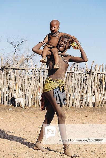 Namibia  Damaraland  junger Mann mit kleinen Kindern auf der Schulter in einem Himba-Dorf