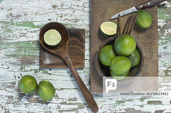 Ganze und geschnittene Limetten und Küchenmesser auf Holz