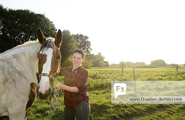 Junge Frau steht auf dem Feld und hält ihr Pferd.