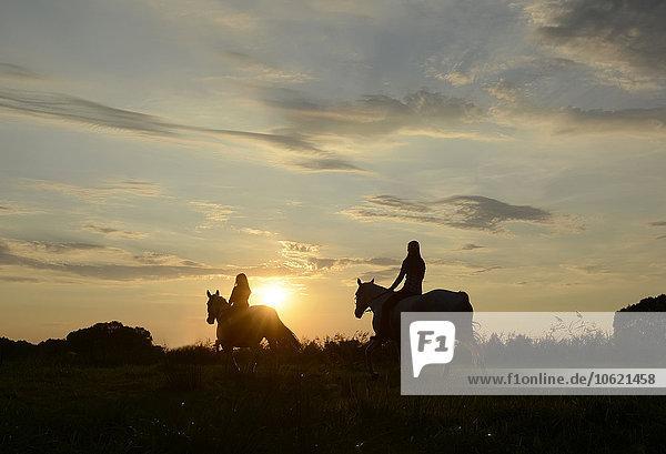 Junge Frauen reiten in den Sonnenuntergang