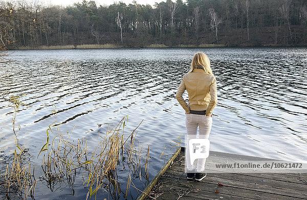 Rückansicht einer blonden Frau  die auf einem Holzsteg steht und einen See betrachtet.