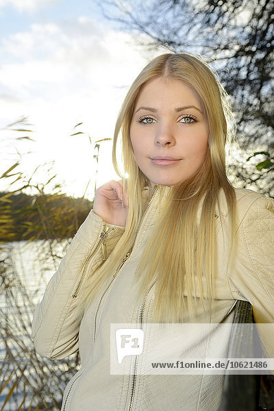 Portrait of young blond woman in front of a lake