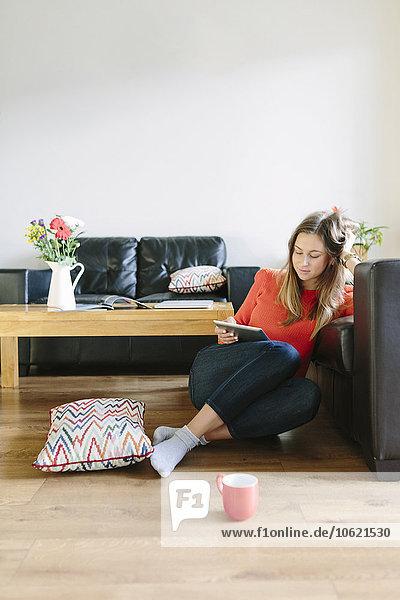 Junge Frau sitzt auf dem Boden ihres Wohnzimmers und schaut auf das digitale Tablett.