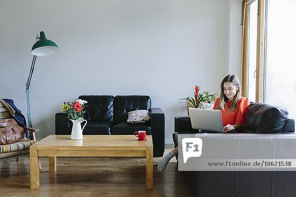Junge Frau mit Laptop entspannt auf der Couch im Wohnzimmer