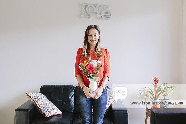 Porträt einer lächelnden jungen Frau mit Blumenstrauß im Wohnzimmer