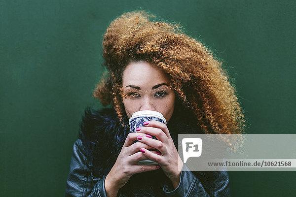 Porträt einer Frau  die Kaffee trinkt  um vor eine grüne Wand zu gehen.