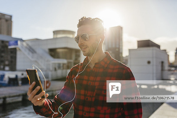 Irland  Dublin  junger Mann am Stadthafen beim Musik hören