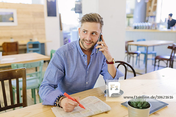 Mann mit Zeitung sitzt in einem Café und telefoniert mit dem Smartphone.
