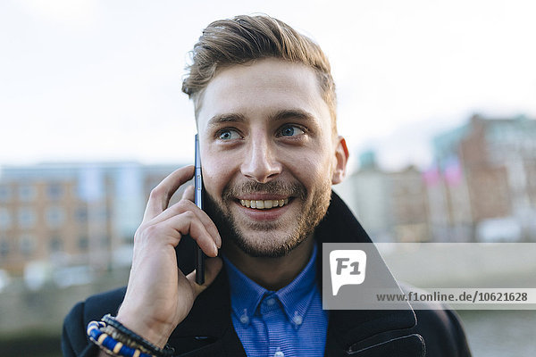 Ireland  Dublin  portrait of smiling young businessman telephoning with smartphone