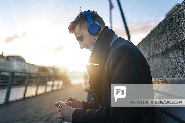 Irland  Dublin  junger Mann sitzt auf einer Bank bei Gegenlicht und hört Musik mit Kopfhörern.