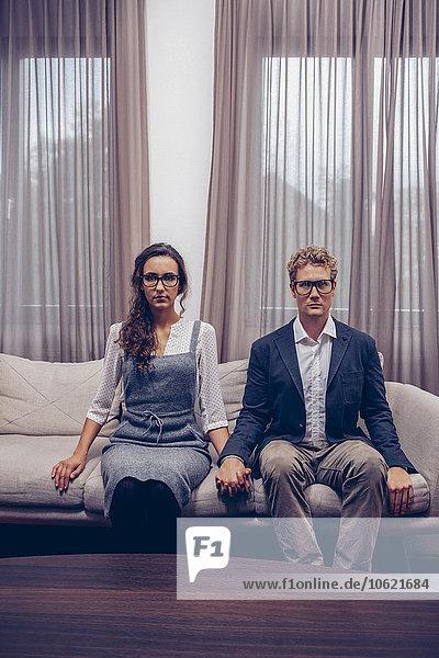 Junges Paar zu Hause auf dem Sofa sitzend mit leerem Gesichtsausdruck