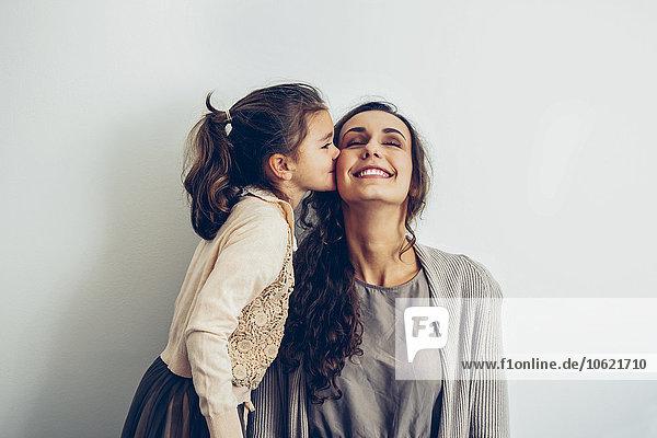 Tochter küsst lächelnde Mutterwange
