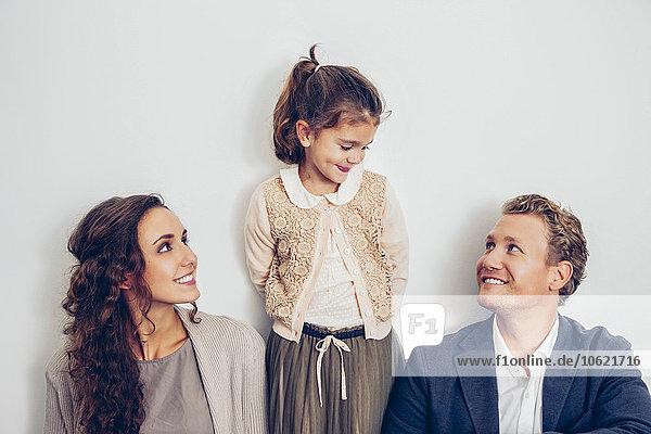 Lächelndes Mädchen  das seinen Vater mit seiner Mutter an der Seite ansieht.